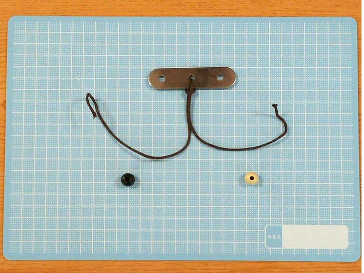 中央の穴に紐をくくった固定金具とビーズ