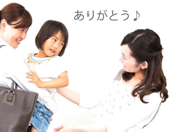ファミリーサポートの人にバイバイする女の子と母親