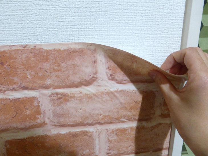 壁にインテリアシールを貼る様子