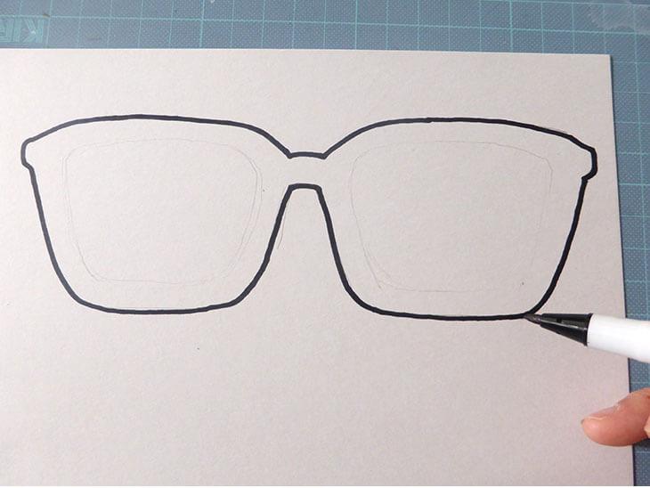 ペンでメガネの輪郭を書いている様子