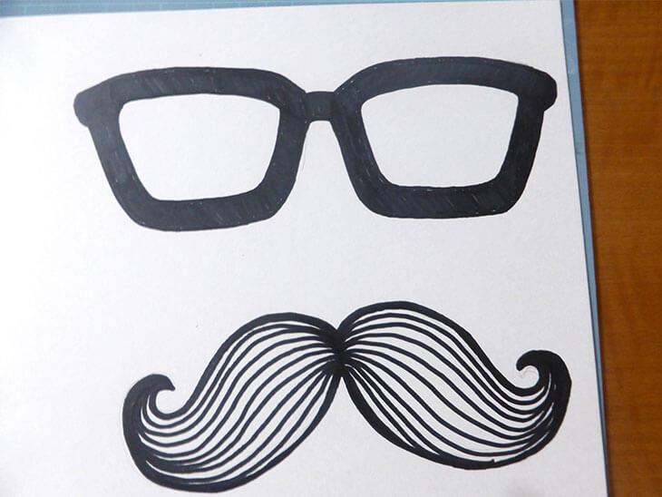 メガネとひげを書いたボール紙