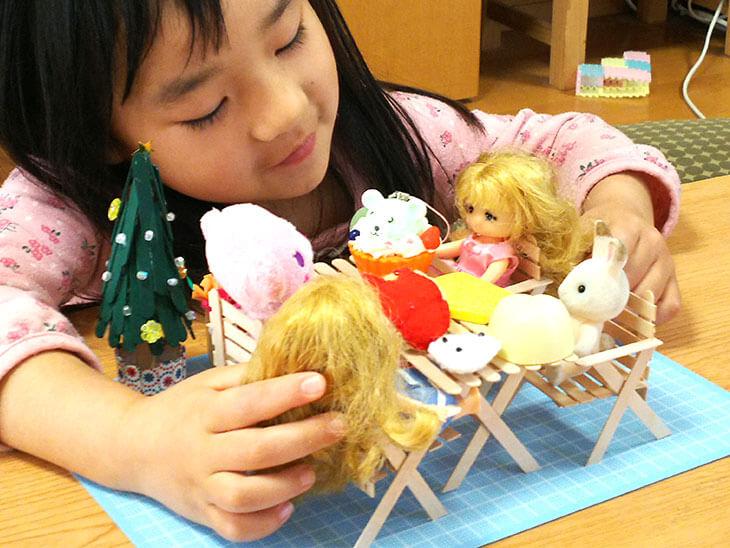 完成したアイス棒工作のミニチュア家具でごっこ遊びをする幼児