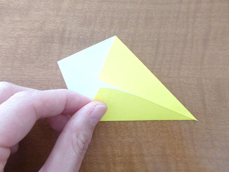 折り目に合わせて折り紙の両側を折っている様子