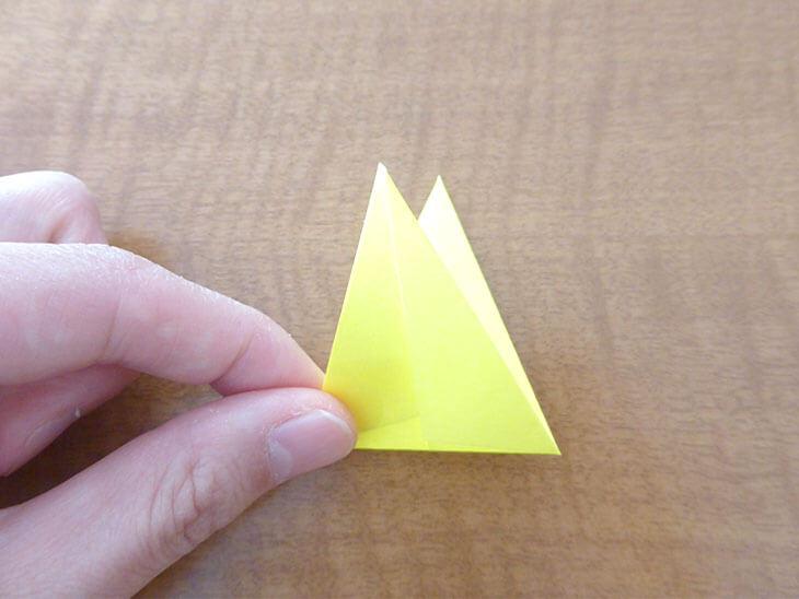 ダイヤ形の折り紙を半分に折っている様子