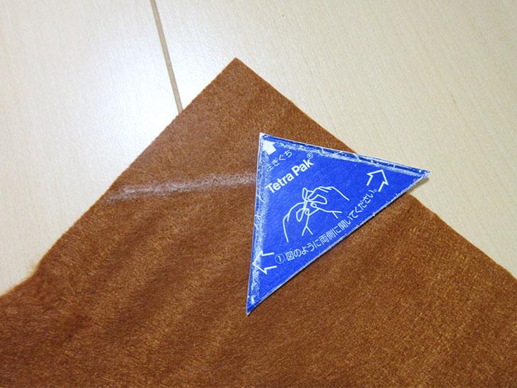 印を付けたフェルトと三角形に切った牛乳パック