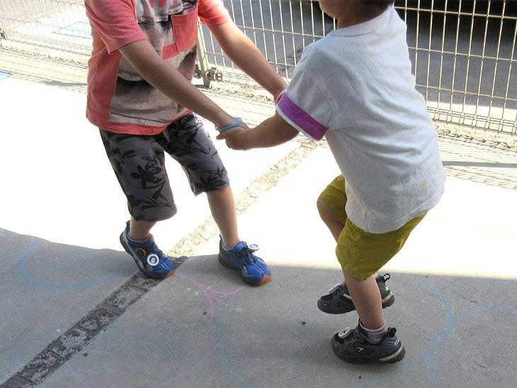 兄弟で手をつないでスキップの練習をする様子