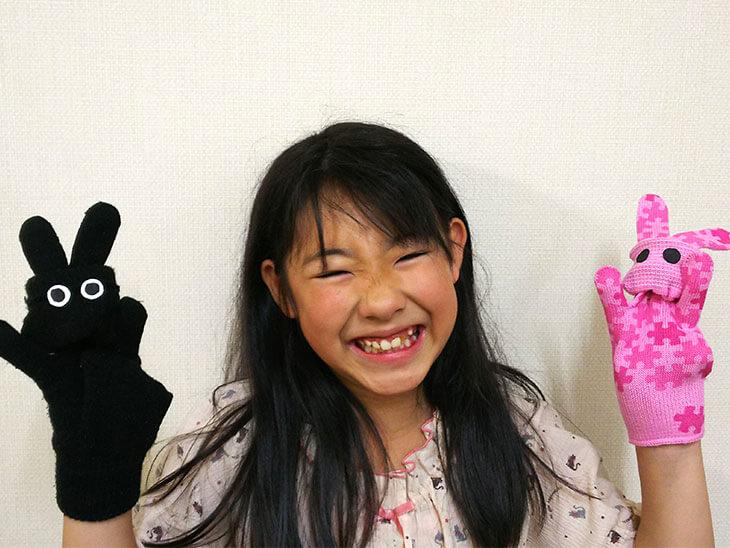 ウサギの手袋パペットを両手につけて遊ぶ子供