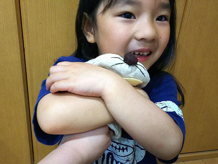 完成したパペットを抱きしめる幼児