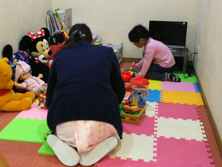 病院のキッズスペースにいる幼児と看護師