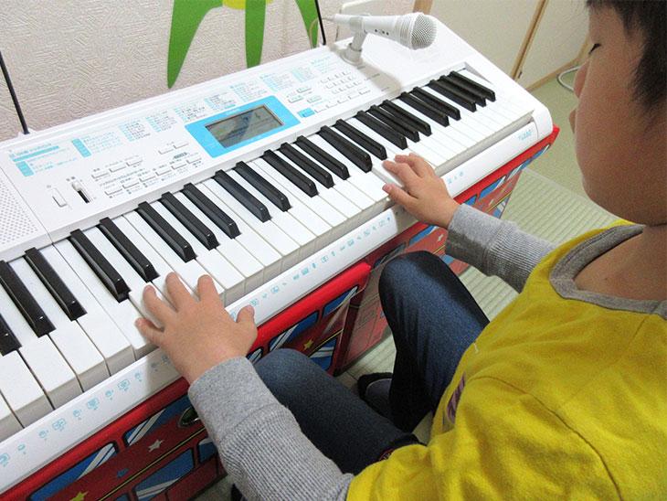 電子ピアノを練習する子供