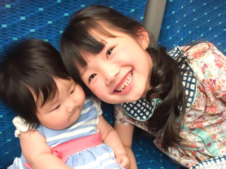 新幹線に乗る赤ちゃんとお姉さん
