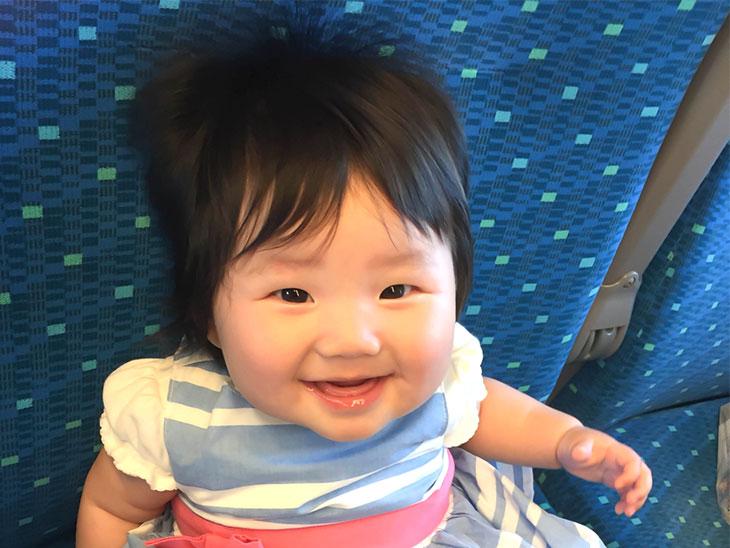 笑顔で新幹線の席に座る赤ちゃん