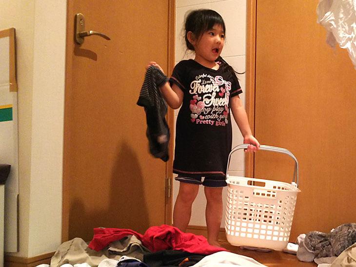洗濯物を散らかすイタズラをする幼児