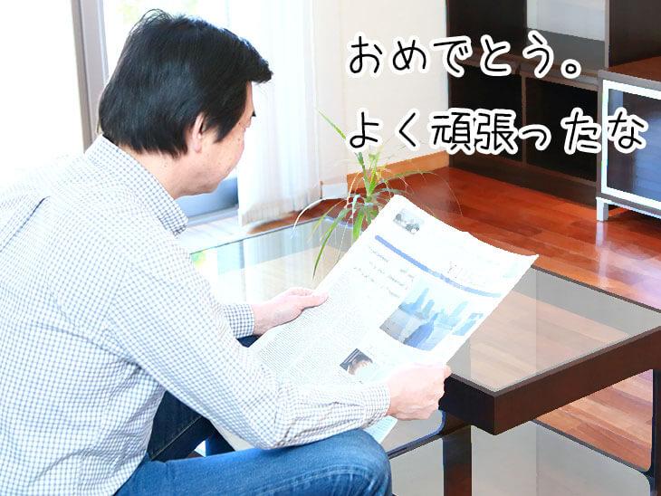 ソファに座って新聞を読んでいる男の人