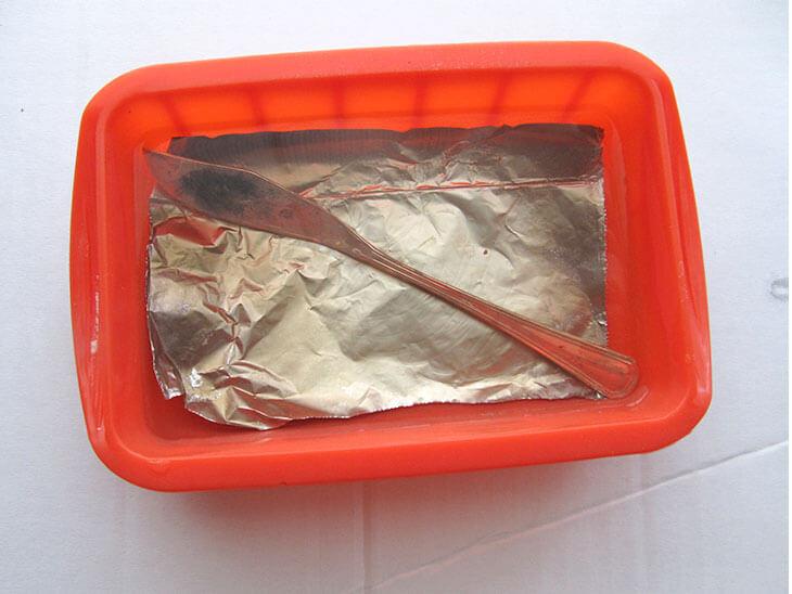 シリコン容器にアルミ箔と銀のバターナイフをつけ置きしている様子