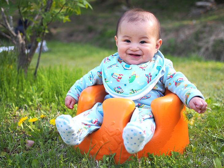 笑顔で芝生の上のバンボに座る赤ちゃん