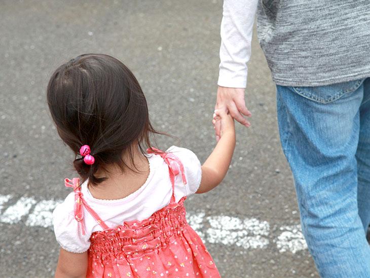 手をつないで歩く親子
