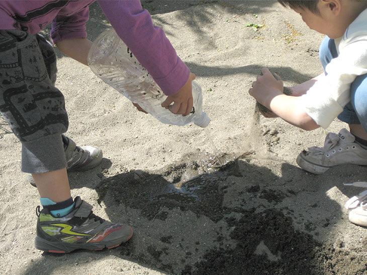 公園の砂場で水遊びをする子供達