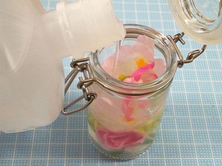 造花の入ったガラス瓶に洗濯のりを注ぐ様子
