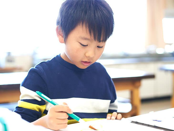 お習字を練習する小学校低学年の男の子