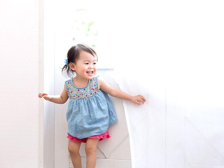カーテンで遊ぶ2歳児の女の子