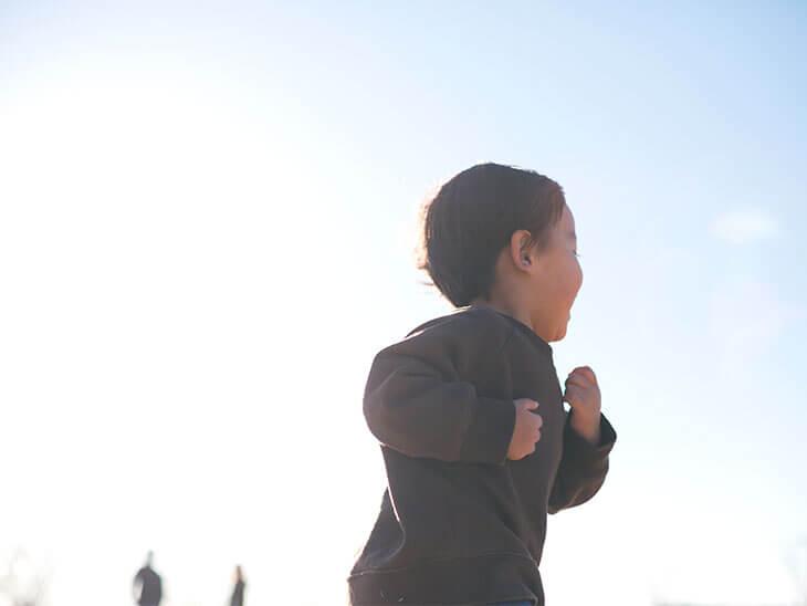 陽の光を浴びて走る男の子