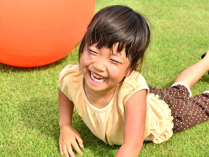 芝生で笑う女の子