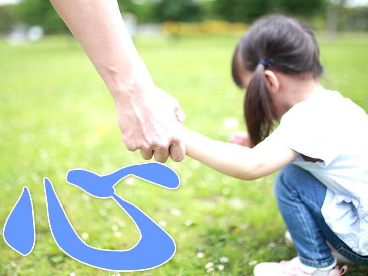 女の子の手を握る親の手と「心」の文字
