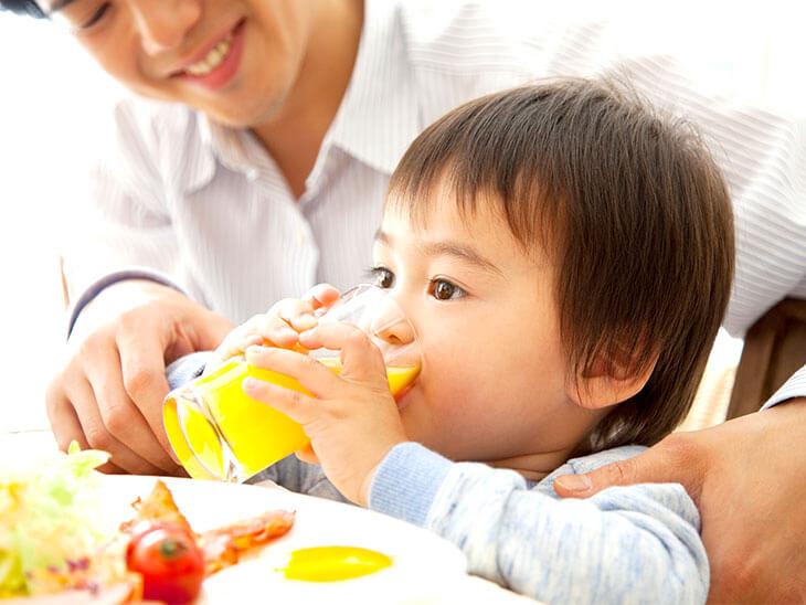 オレンジジュースを飲む男の子