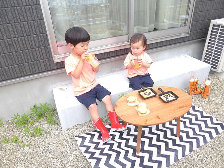 外でバーベキュースイーツを食べながらジュースを飲む子供
