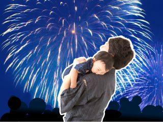 花火大会で赤ちゃんを抱っこする父親