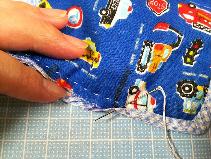 ダブルガーゼ側のバイアステープをまつり縫いする様子