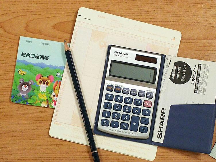 子供の通帳と電卓と鉛筆
