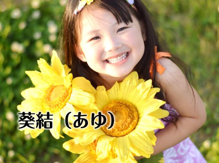 向日葵を抱えて笑う女の子
