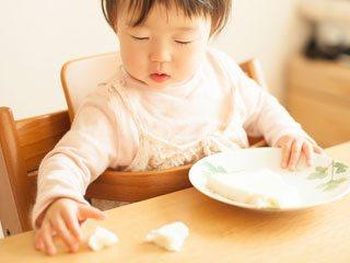 こぼれたご飯を摘む赤ちゃん