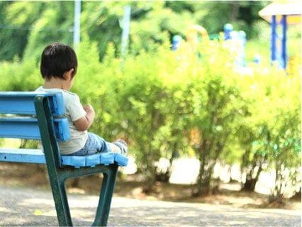 ベンチに座る迷子の男の子