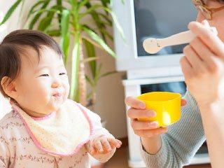 母親から離乳食をもらう赤ちゃん