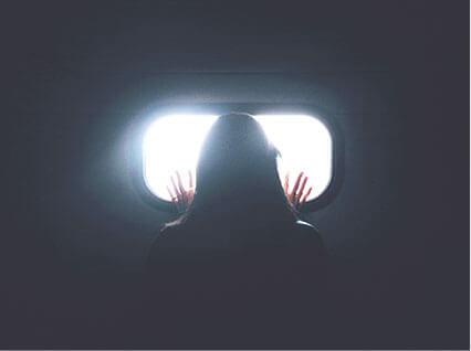小さな窓から外を見る女性