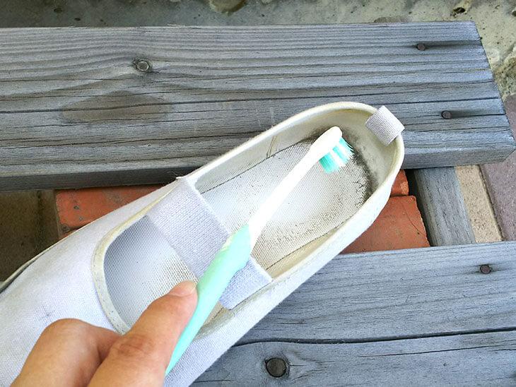 上履きのホコリ汚れを歯ブラシで取る様子