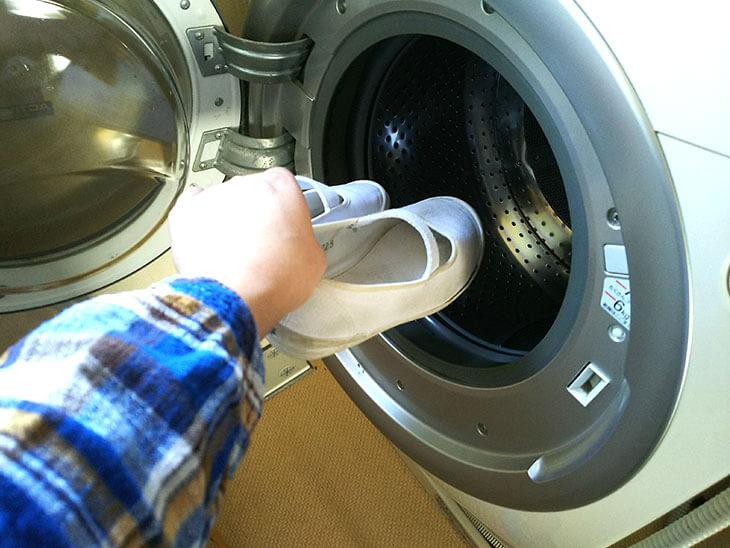 靴を洗濯機に入れる様子