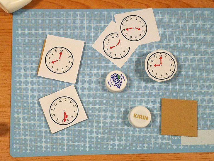 時計イラストのマグネットパーツと四角く切ったダンボール