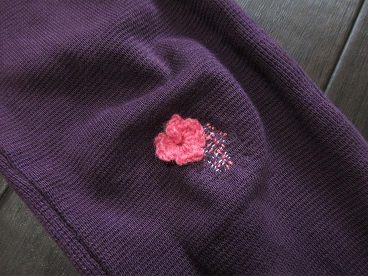 穴を目立つ糸と小さなモチーフで補修した子供のズボン