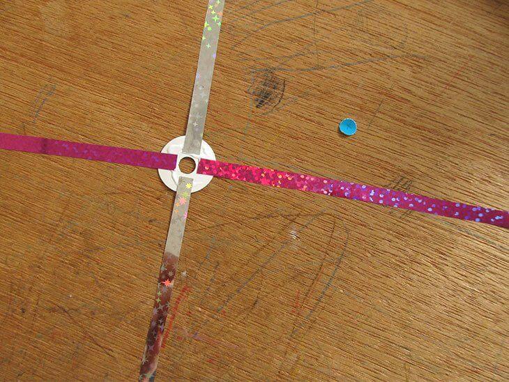 カットしたキラキラホログラムチェーンを十字に貼った丸シールの接着面