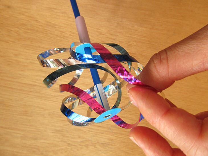 割れないシャボン玉おもちゃの軸を少し動かしながら絡まったテープを直す様子