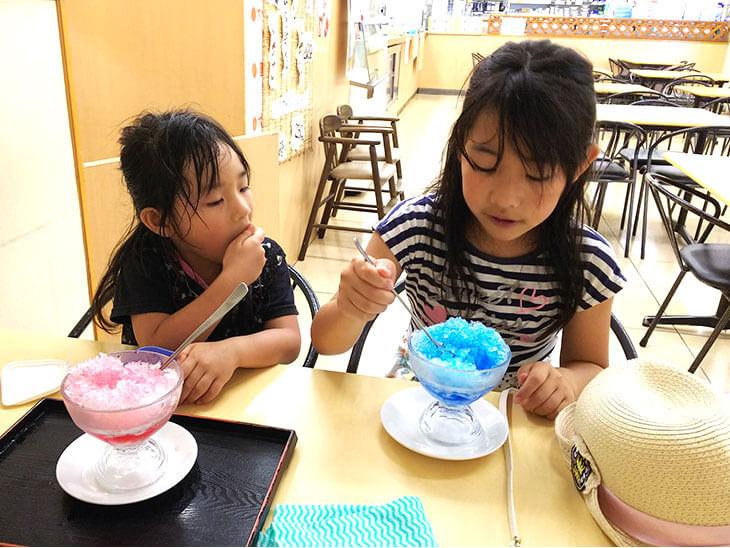 合成着色料のシロップを使ったかき氷を食べる子供の写真