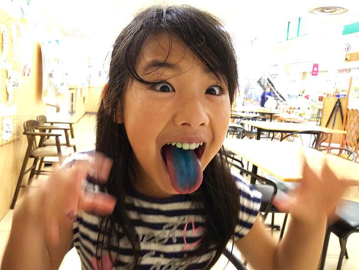 着色料で染まった舌を見せる子供