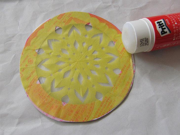 ローズウィンドウ枠に切ったお花紙を貼り付ける様子