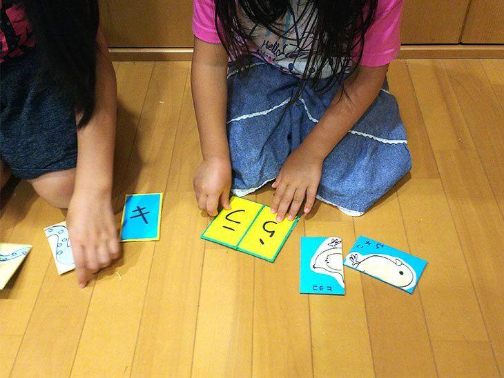 絵合わせカードで文字合わせをする子供