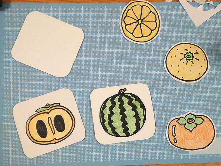 カットしたマグネットに絵合わせカード用のイラストを貼る様子
