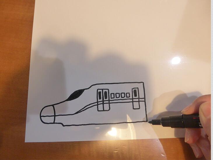 白いプラバンにおもちゃの新幹線を描いている様子